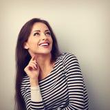 Gelukkige emotionele vrouw die en omhoog met toothy smilin denken kijken royalty-vrije stock foto's