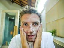 Gelukkige en aantrekkelijke Kaukasische mens die verse thuis badkamers glimlachen die zijn gezicht met exfoliant zeep wassen die  stock foto