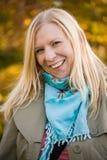 Gelukkige en aantrekkelijke vrouw die in herfstbos glimlachen stock afbeeldingen