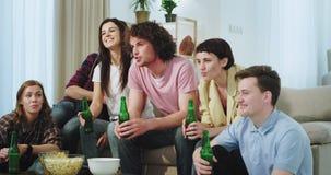 Gelukkige en enthousiaste vrienden die op iets letten interesserend op het TV-het drinken bier en samen binnen het genieten van d stock footage