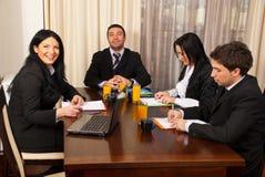 Gelukkige en ernstige bedrijfsmensen op vergadering Stock Afbeelding