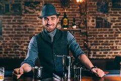 Gelukkige en glimlachende barman die cocktails voorbereiden en van het werken genieten bij bar Royalty-vrije Stock Afbeelding