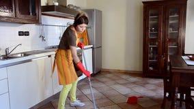 Gelukkige en huisvrouw die schoonmaken dansen