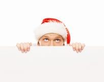 Gelukkige en knappe tienerkerel in een Kerstmishoed en een banner Stock Afbeeldingen