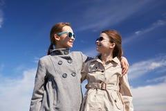 Gelukkige en meisjes die in openlucht koesteren spreken Stock Foto's