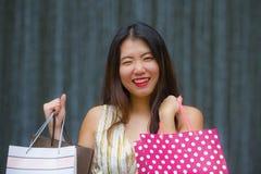 Gelukkige en mooie Aziatische Koreaanse vrouw die op straat het stellen op achtergrond lopen die vrolijke dragende het winkelen z stock afbeelding