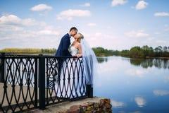 Gelukkige en mooie bruidegom en bruid tedere kus bij de lenteoutdoo Stock Foto's