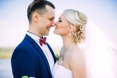 Gelukkige en mooie bruidegom en bruid tedere kus bij de lenteoutdoo Stock Afbeeldingen