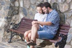 Gelukkige en Positieve Kaukasische Paarzitting samen met Smartphone en het Luisteren aan Muziek stock fotografie