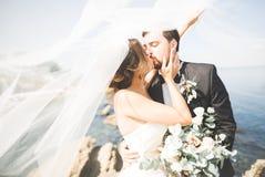 Gelukkige en romantische scène van enkel het gehuwde jonge huwelijkspaar stellen op mooi strand Stock Afbeeldingen