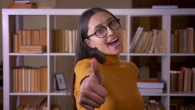 Gelukkige en verrukte donkerbruine vrouwelijke leraarsgebaren duim-op teken als en eerbied bij de bibliotheek te tonen stock videobeelden