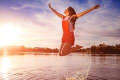 Gelukkige en vrije jonge vrouw die en wapens op rivierbank springen opheffen Vrijheid Actieve levensstijl stock fotografie
