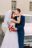 Gelukkige enkel echtpaarholding elkaar op de achtergrond van uitstekende auto royalty-vrije stock foto
