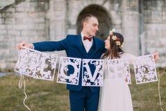 Gelukkige enkel gehuwde bruid en bruidegom die de artistieke brieven van de papercutliefde houden Royalty-vrije Stock Fotografie