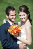 Gelukkige enkel gehuwde bruid en bruidegom op groene grasachtergrond Royalty-vrije Stock Afbeelding