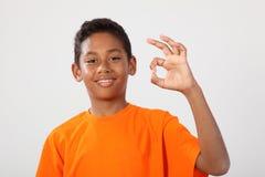 Gelukkige etnische schooljongen 11 maakt o.k. hand ondertekenen Royalty-vrije Stock Afbeelding