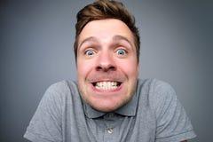 Gelukkige Europese mens die tanden dichtklemmen bij camera royalty-vrije stock fotografie