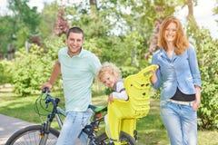 Gelukkige familie berijdende fiets bij het park Royalty-vrije Stock Afbeeldingen