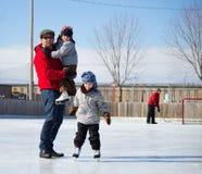Gelukkige familie bij de het schaatsen piste Stock Afbeelding
