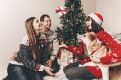 Gelukkige familie bij modieuze sweaters en leuke hond die pret met gi hebben stock fotografie