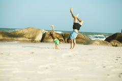 Gelukkige familie bij strand het spelen, vader met zoon het lopen overzeese kust, rotsen achter het glimlachen nemende vakantie stock foto's