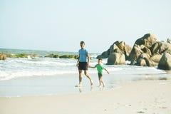 Gelukkige familie bij strand het spelen, vader met zoon het lopen overzeese kust, rotsen achter het glimlachen nemende vakantie stock fotografie