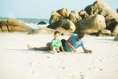 Gelukkige familie bij strand het spelen, vader met zoon het lopen overzeese kust, rotsen achter het glimlachen nemende vakantie stock afbeeldingen
