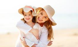 Gelukkige familie bij strand moeder en kinddochteromhelzing bij zonsondergang Royalty-vrije Stock Foto's