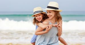 Gelukkige familie bij strand moeder en kinddochteromhelzing op zee royalty-vrije stock foto