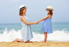 Gelukkige familie bij strand moeder en kinddochteromhelzing op zee stock afbeelding