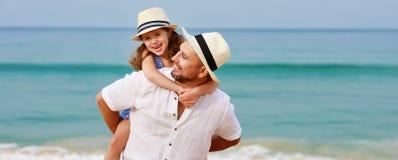 Gelukkige familie bij strand vader en kinddochteromhelzing op zee royalty-vrije stock foto's