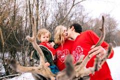 Gelukkige familie bij zonsondergang Vader, moeder en kind de dochters hebben pret en spelen op sneeuw de wintergang in aard, kus  royalty-vrije stock afbeeldingen