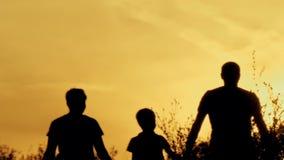 Gelukkige familie bij zonsondergangsilhouet stock footage