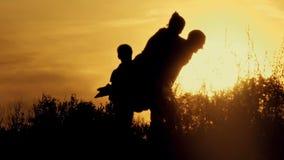 Gelukkige familie bij zonsondergangsilhouet stock videobeelden