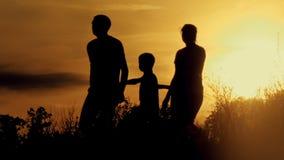 Gelukkige familie bij zonsondergangsilhouet stock video