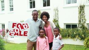 Gelukkige familie buiten hun nieuw huis stock footage