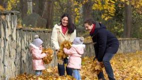 Gelukkige familie in de herfstpark Moeder, vader en twee meisjes stock footage