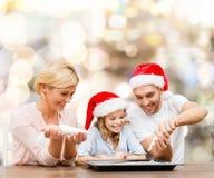 Gelukkige familie in de hoeden van de santahelper het koken Stock Foto