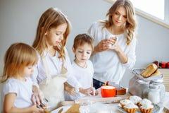 Gelukkige familie in de keuken De moeder en haar leuke jonge geitjes koken koekjes stock foto's
