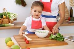 Gelukkige familie in de keuken Moeder en kinddochter die smakelijke het meest breakfest van verse salade koken Weinig helper snij Royalty-vrije Stock Afbeelding