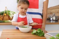 Gelukkige familie in de keuken Moeder en kinddochter die smakelijke het meest breakfest van verse salade koken Weinig helper snij Stock Foto