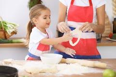 Gelukkige familie in de keuken Moeder en kindpastei of koekjes van de dochter de de kokende vakantie voor Moedersdag Royalty-vrije Stock Afbeelding
