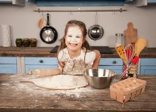 Gelukkige familie in de keuken De moeder toont haar dochterbakkerij die zij samen hebben gemaakt Eigengemaakt voedsel, weinig hel royalty-vrije stock foto