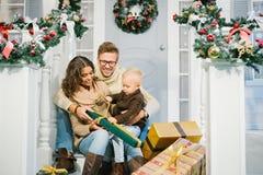 Gelukkige familie - de moeder, de vader en de zoon pakken de Kerstmisgiften uit Stock Foto