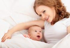 Gelukkige familie. De moeder en de baby liggen en omhelzen onder deken Royalty-vrije Stock Foto's