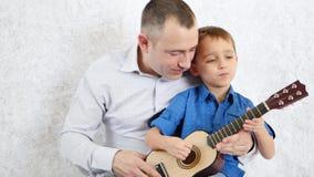 Gelukkige familie: de vader en de zoon spelen de gitaar en zingen Het voelen van de emoties van geluk, liefde, vreugde en glimlac stock footage
