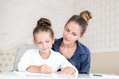 Gelukkige Familie  De volwassen vrouw helpt het kindmeisje royalty-vrije stock fotografie