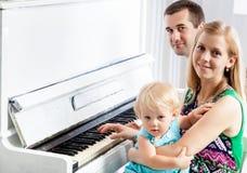 Gelukkige familie dichtbij de piano stock fotografie