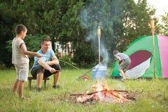 Gelukkige familie dichtbij kampvuur roosterende worsten Stock Foto's
