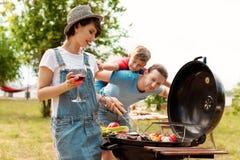 Gelukkige familie die barbecue met moderne grill hebben royalty-vrije stock afbeeldingen